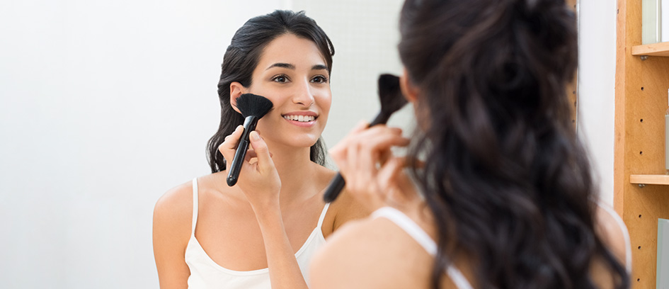 Woman applying makeup while looking in a mirror