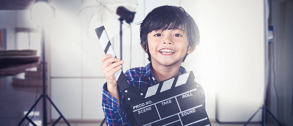 A child actor holding a clapboard