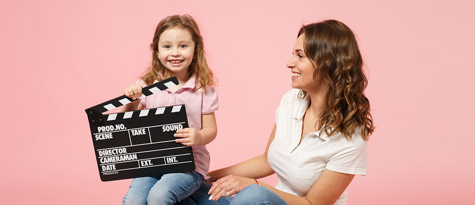 A mother and daughter with a clapper board on a pink background.