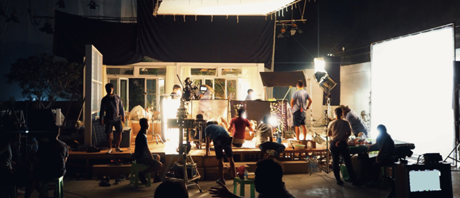 Crew setting up cinematic lighting on film set