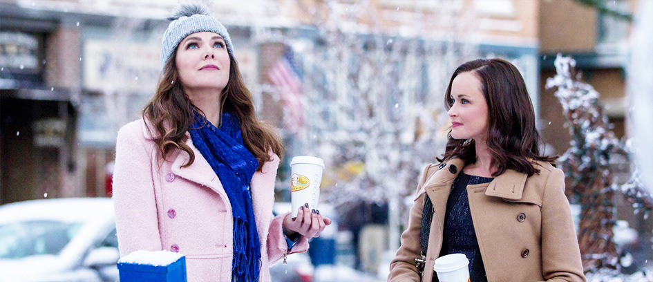 Two women holding coffee in the snow.