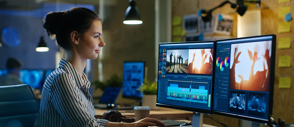 Woman film editing on two computer screens