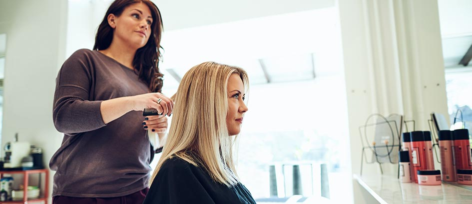 Blonde woman getting her hair length trimmed