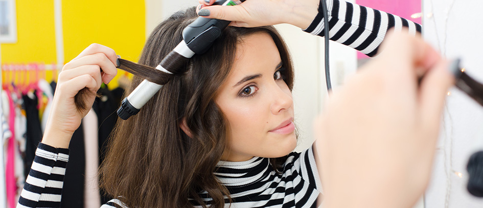Brunette woman curling her hair