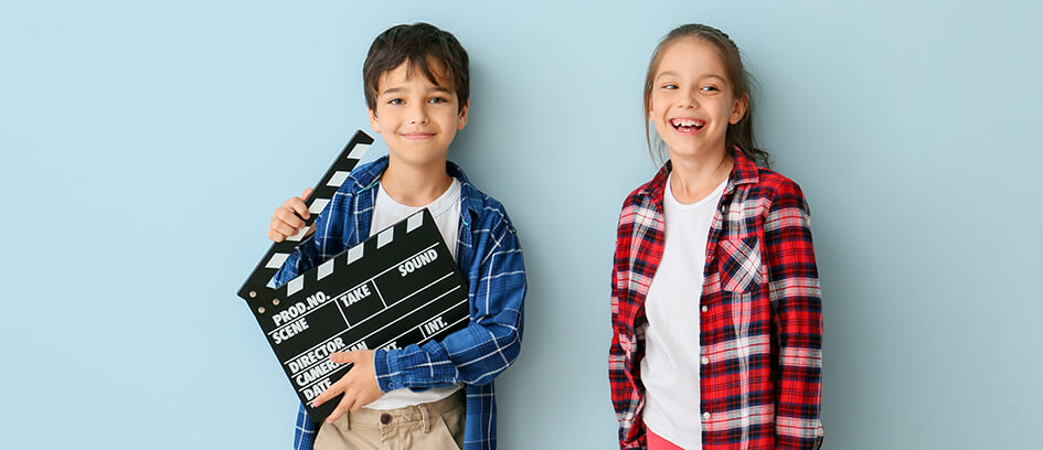 A boy holding a clapperboard and a young girl smiling