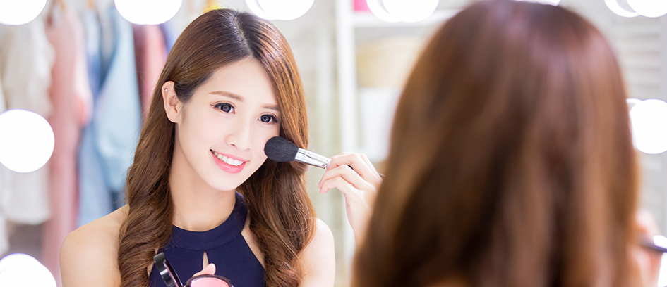 Woman looking in mirror applying makeup basics like blush