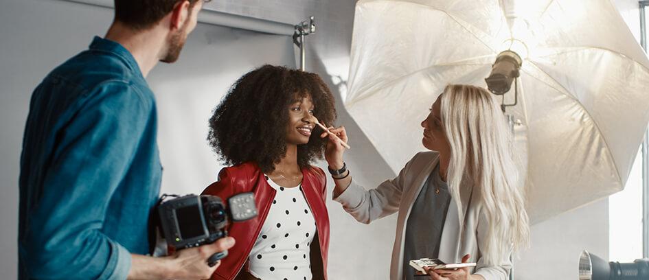 Makeup artist applying makeup to an actor on set.