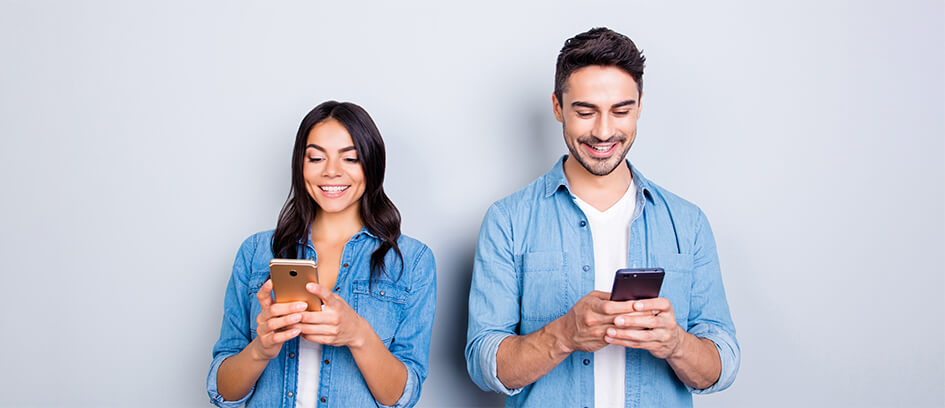 A man and woman looking at Central Casting messages on their phones.