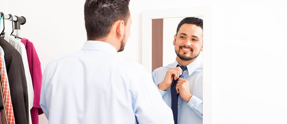 Man looking in mirror tying a tie.