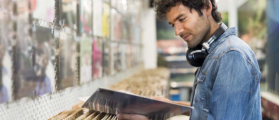 Man with headphones looking through records for TV songs