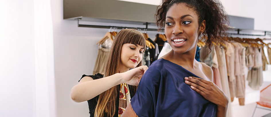 Costumer measuring a woman for wardrobe essentials