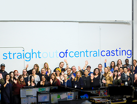 Central Casting staff members waving in front of straight out of Central Casting sign
