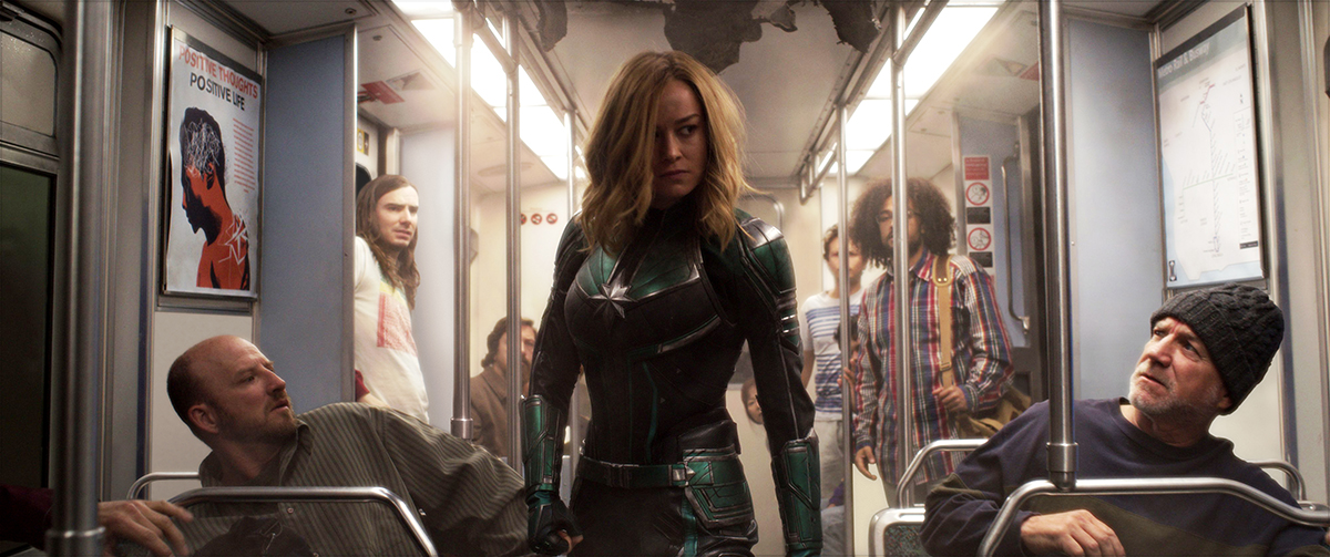 Slide 1 shows Captain Marvel on a subway car full of people and slide 2 shows Captain Marvel alone on the same subway car.
